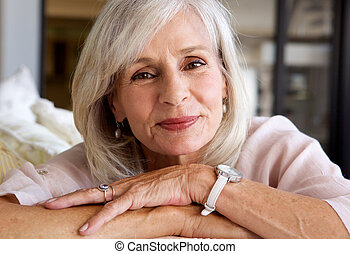 relaxed older woman smiling and sitting on sofa