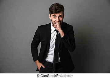 Close-up portrait of scared man in black suit bites his fist, looking at camera