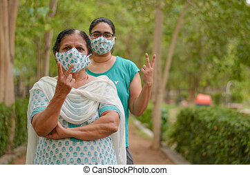 Close up Portrait of senior Indian lady and young lady wearing matching surgical cotton mask to protect themself from Corona Virus (COVID-19) pandemic showing V victory signs in a park in Delhi, India