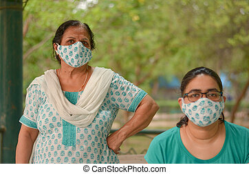 Close up Portrait of senior Indian lady and young lady wearing matching surgical cotton mask to protect themself from Corona Virus (COVID-19) pandemic in a park in New Delhi, India
