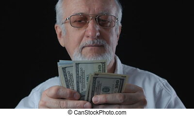 portrait of senior man in a white shirt counts dollar bills