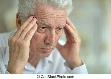 Close-up portrait of senior man with headache