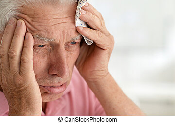 Close up portrait of senior man with headache