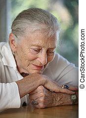 Close-up portrait of senior woman contemplating. Shallow DOF...