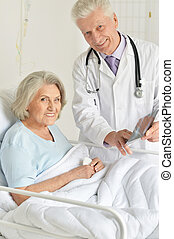 Close up portrait of senior woman in hospital with caring doctor