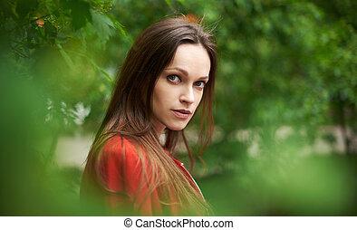 Close up portrait of sensitive woman in the city park