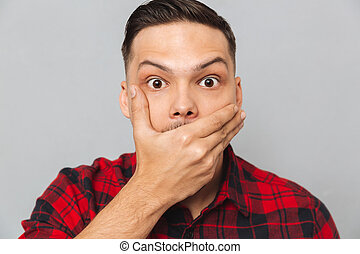 Close up portrait of Shocked man covering his mouth