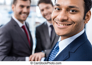 Close-up portrait of smiling african american businessman looking at camera with colleagues standing behind, business concept