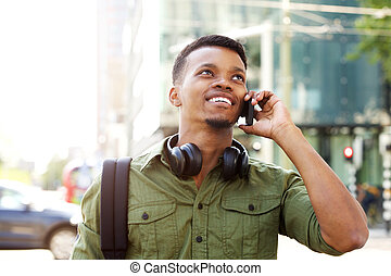 smiling african american man talking on cellphone in the city