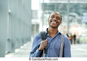 smiling african businessman standing bag in building