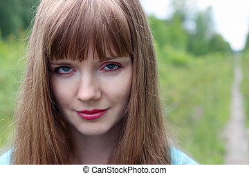 Close up portrait of smiling beautiful young woman at summer day