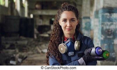 Close-up portrait of smiling girl graffiti artist standing...