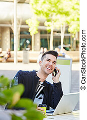 smiling man on telephone call at cafe with laptop
