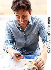 smiling man reading text message on smart phone with cup of coffee