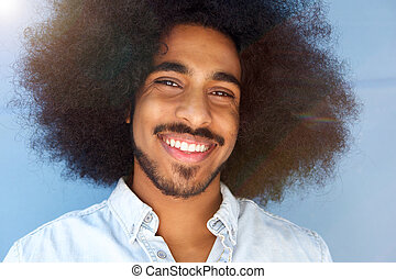 smiling man with afro and beard by blue wall