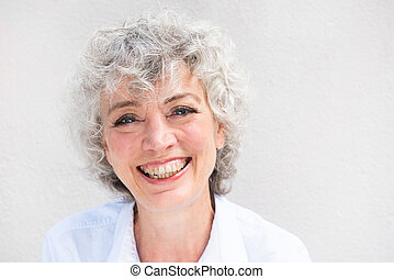 Close up portrait of smiling older woman by white background