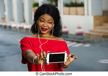Close-up portrait of smiling woman holding phone with black scre