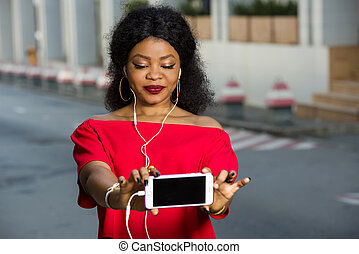 Close-up portrait of smiling woman holding phone with black screen.