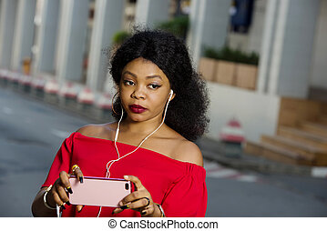 Close-up portrait of smiling woman holding the phone.