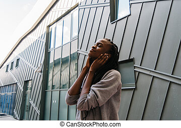 Close-up portrait of smiling young african american woman listening to music on headphones outdoors, modern building as background