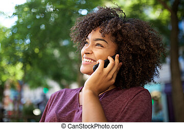 smiling young african american woman talking with cellphone outdoors