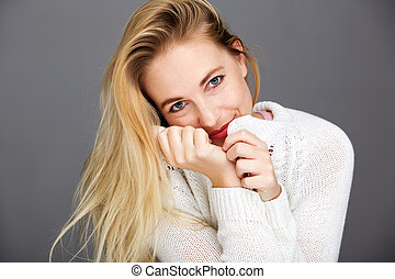 smiling young blond woman with white cardigan