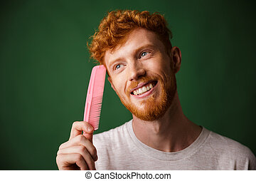Close-up portrait of smiling young readhead beardy man with pink comb