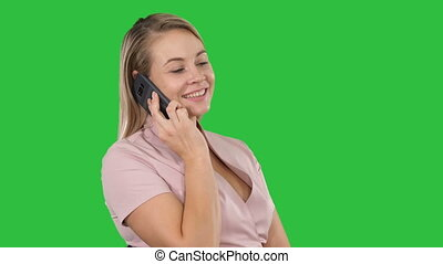 Portrait of smiling young woman making a call sitting on a Green Screen, Chroma Key.