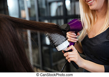 Close-up portrait of stylist drying woman hair in salon
