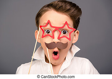 Close up portrait of surprised funny schoolboy holding props