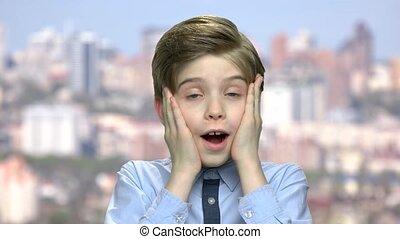 Close up portrait of surprised little boy.