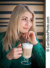 Close-up portrait of the beautiful woman with a coffee