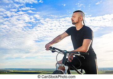 Close-up portrait of the cyclist against beautiful blue sky with clouds.