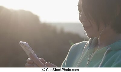 Close-up portrait of the young asian girl with shot dark hair chatting via the mobile phone in the sun. Outdoor concept.