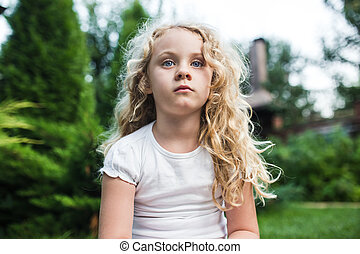 Close-up portrait of thoughtful little girl with long blond hair