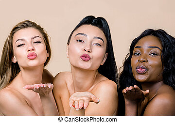 Close up portrait of three smiling ladies of different races and skin colour, Caucasian, Asian and African, making air kisses at camera, posing on beige studio background. Love and beauty concept