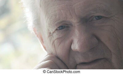 Close up portrait of tired happy old man smiling at camera