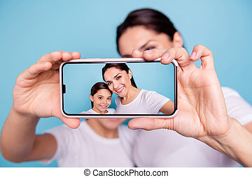 Close-up portrait of two nice people wearing casual white t-shirt holding in hands device making taking selfie photo screen isolated over blue pastel background