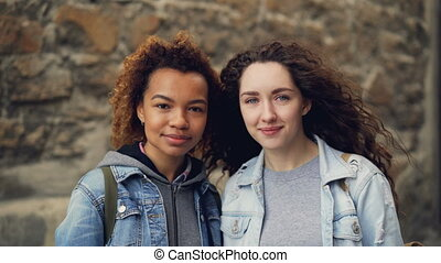 Close-up portrait of two pretty young women friends standing...