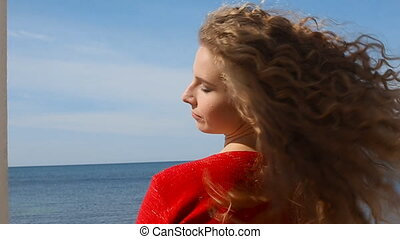 Close up portrait of woman running hand through curly hair...