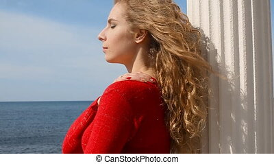 Close up portrait of woman running hand through curly hair blowing in wind by sea on beach. Happy female over blue sky.