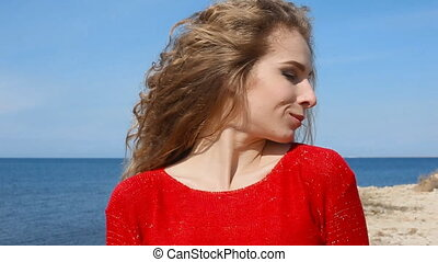 Close up portrait of woman running hand through curly hair blowing in wind by sea on beach. Happy female over blue sky