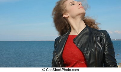 Close up portrait of woman take off black leather jacket, trendy female with curly hair blowing in wind by sea on beach. Happy female over blue sky.