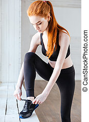 Close-up portrait of woman tying shoelaces in the gym