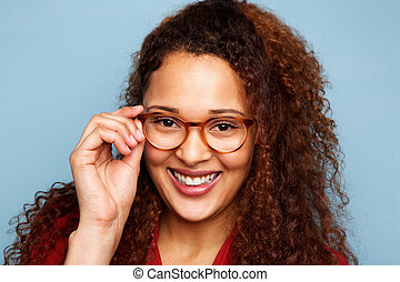 woman with glasses and curly hair smiling against blue background