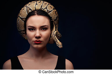 Close up portrait of woman with snake around her head on dark background