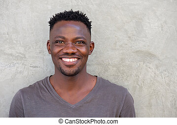 young african american man smiling by wall