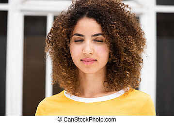 Close up portrait of young african american woman with curly hair and eyes closed