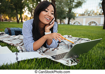 Close-up portrait of young asian female student talking on mobile phone, looking at laptop screen, outdoor