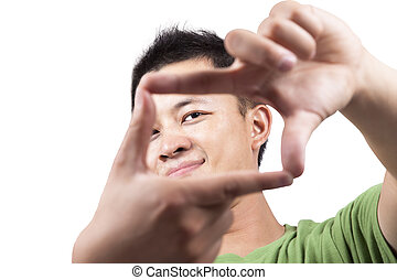 Close-up portrait of young asian man looking through framed hands